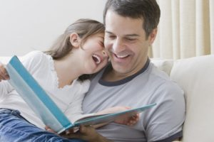 Hispanic father reading book to daughter