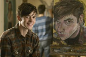 Art student alongside his self portrait